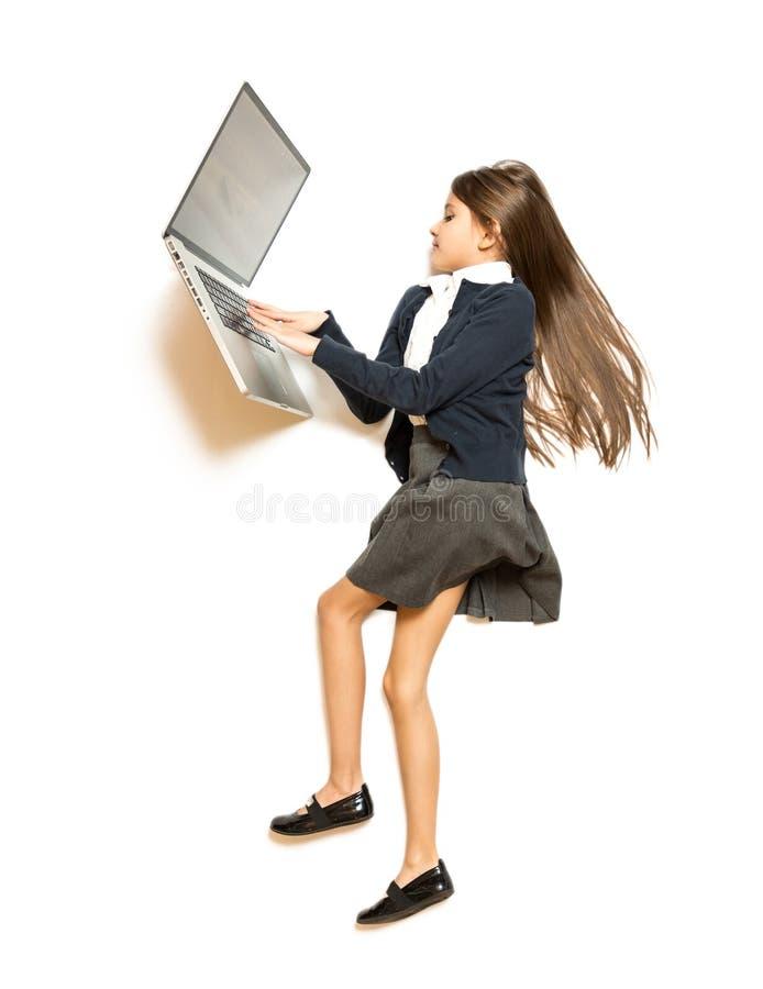 Φωτογραφία από την κορυφή χαριτωμένο να βρεθεί κοριτσιών στο πάτωμα και της χρησιμοποίησης του lap-top στοκ φωτογραφίες
