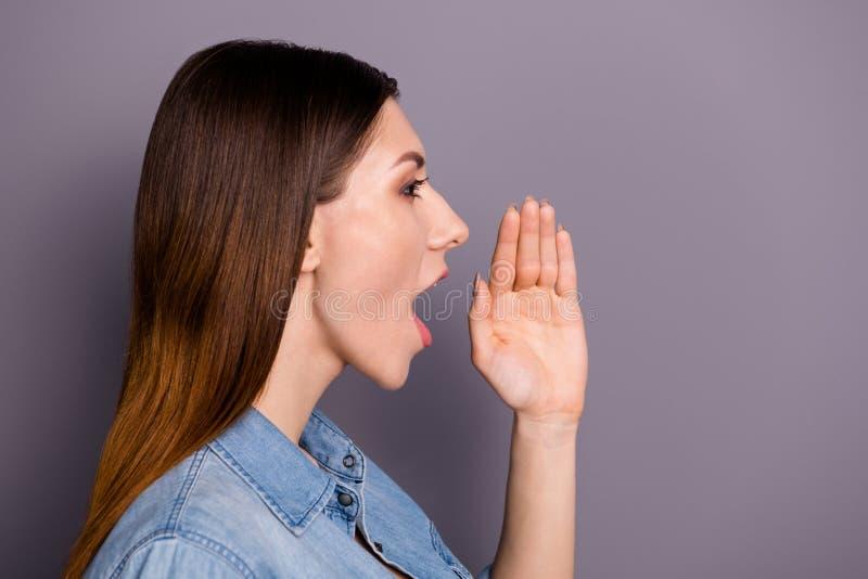 Φωτογραφία από την πλευρά προφίλ της χαριτωμένης όμορφης κυρίας κρατώντας το χέρι κοντά στο στόμα ουρλιαχτό που φωνάζει, κοινή χρ στοκ εικόνες