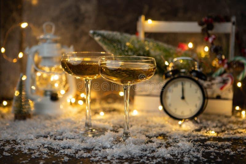 Φωτογραφία δύο γυαλιών σαμπάνιας στο θολωμένο υπόβαθρο με το χριστουγεννιάτικο δέντρο, φανάρι, ρολόι στοκ φωτογραφία με δικαίωμα ελεύθερης χρήσης