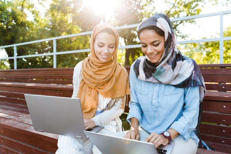 Φωτογραφία δύο ισλαμικών κοριτσιών που φορούν headscarfs τη στήριξη στο πράσινο πάρκο στοκ εικόνες με δικαίωμα ελεύθερης χρήσης
