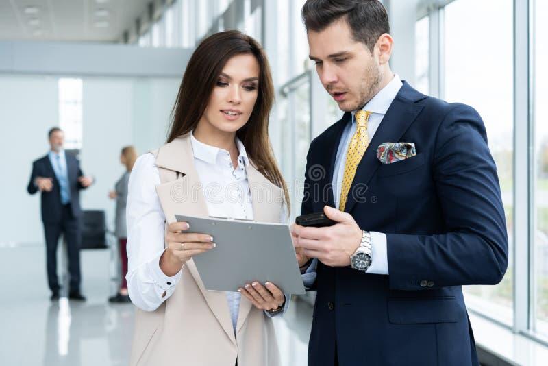 Φωτογραφία δύο συναδέλφων που συζητούν για το πρόγραμμα στο γραφείο στοκ φωτογραφία με δικαίωμα ελεύθερης χρήσης