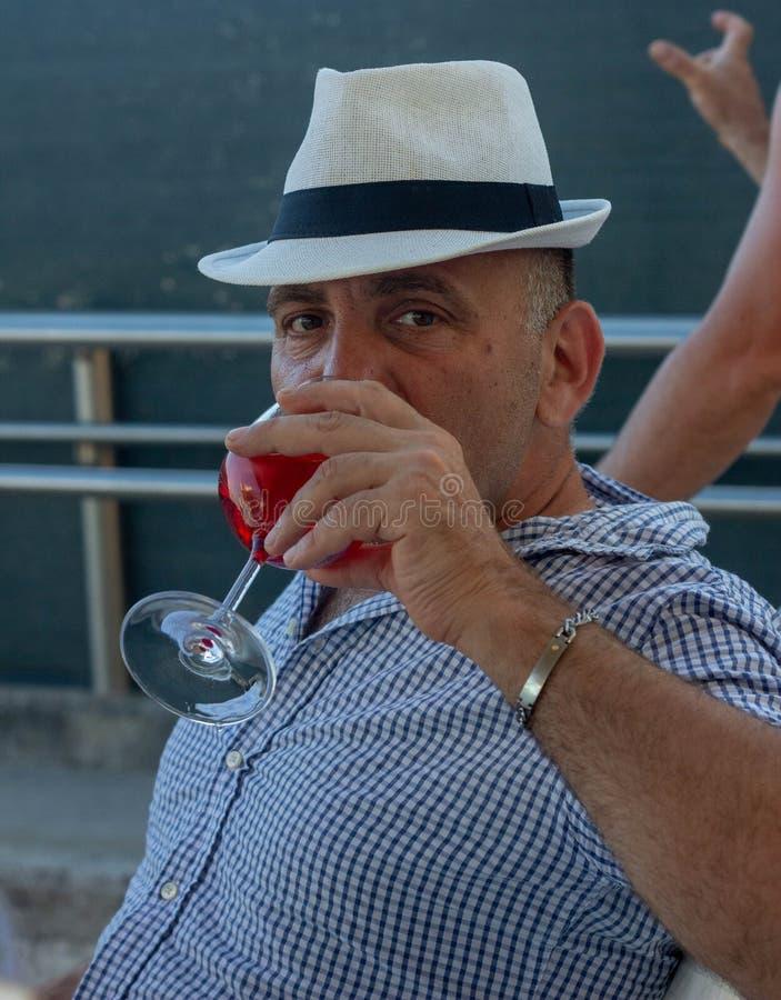 Φωτογραφία ενός ατόμου με ένα καπέλο που πίνει ένα απεριτίφ στοκ φωτογραφίες