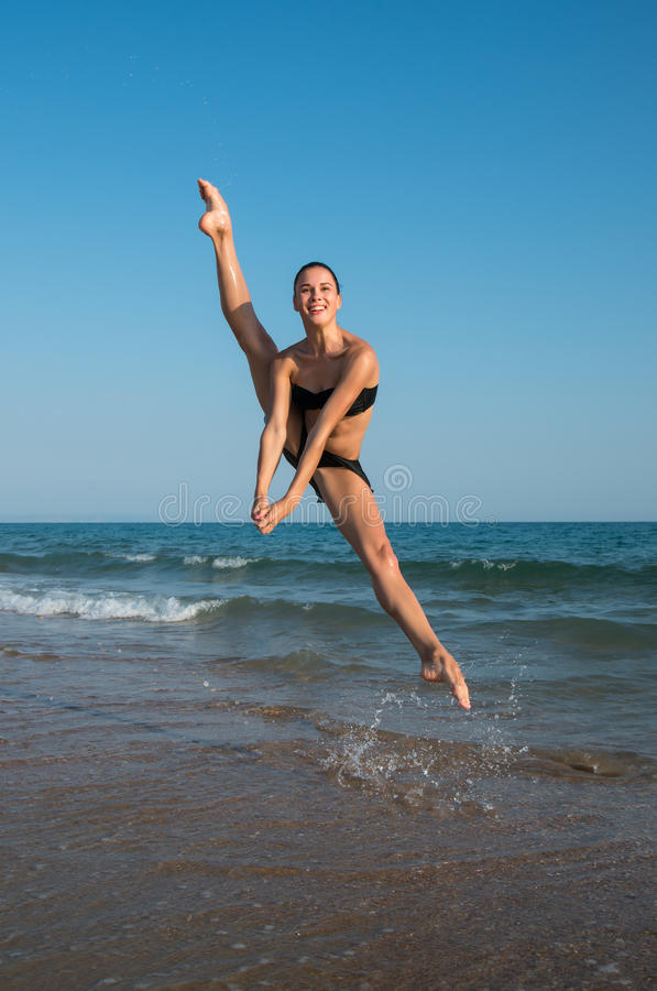 Φωτογραφία ενός όμορφου θηλυκού χορευτή που πηδά σε μια παραλία στο τ στοκ φωτογραφία με δικαίωμα ελεύθερης χρήσης