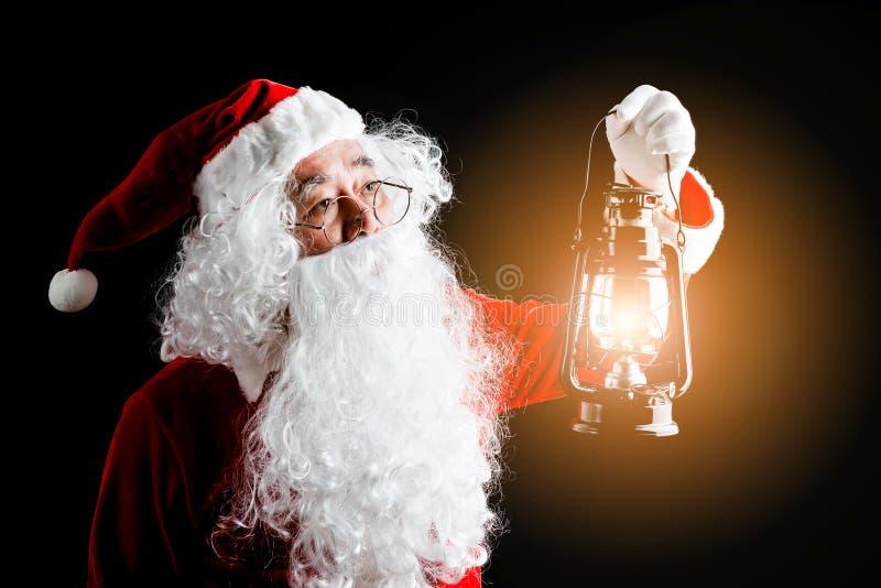 Φωτογραφία ευτυχούς Άγιου Βασίλη με ένα φανάρι του χριστουγεννιάτικου δώρου στα χέρια, που απομονώνεται στο μαύρο υπόβαθρο στοκ φωτογραφία