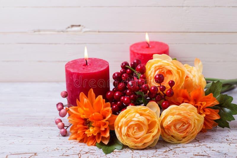 Φωτογραφία ζωής φθινοπώρου ακόμα με τα λουλούδια στα κίτρινα χρώματα και candl στοκ εικόνες
