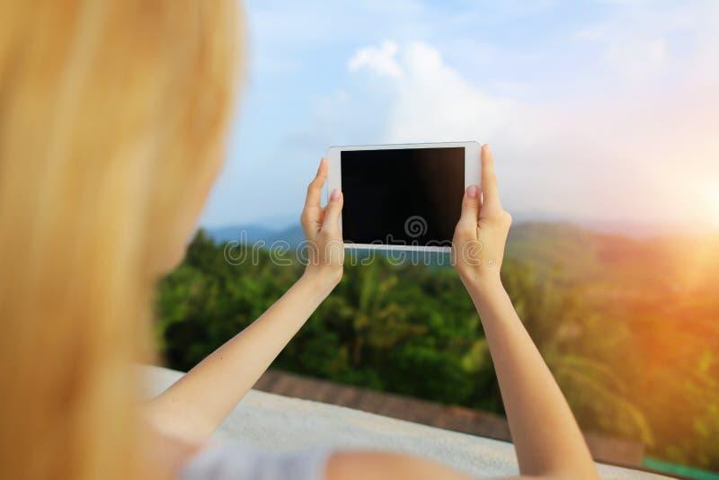 Φωτογραφία ηλιοφάνειας της γυναίκας χρησιμοποιώντας την ταμπλέτα και παίρνοντας τη φωτογραφία των βουνών της Ταϊλάνδης στοκ εικόνες
