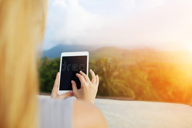Φωτογραφία ηλιοφάνειας του θηλυκού προσώπου χρησιμοποιώντας την ταμπλέτα και παίρνοντας τη φωτογραφία των βουνών της Ταϊλάνδης στοκ εικόνες