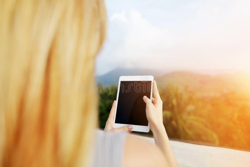 Φωτογραφία ηλιοφάνειας του κοριτσιού χρησιμοποιώντας την ταμπλέτα και παίρνοντας τη φωτογραφία των βουνών της Ταϊλάνδης στοκ εικόνες