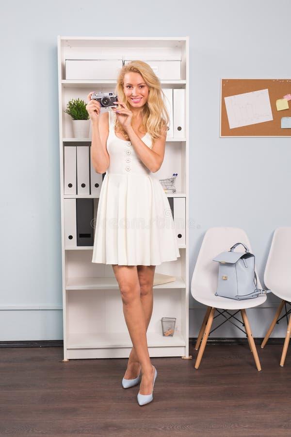 Φωτογραφία και έννοια ανθρώπων - κάθετο πορτρέτο της όμορφης γυναίκας στο άσπρο φόρεμα που κρατά το εκλεκτής ποιότητας photocamer στοκ φωτογραφία