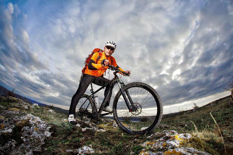 Φωτογραφία κατώτατης άποψης του ποδηλάτη στο πορτοκαλί σακάκι που στέκεται με το ποδήλατό του στο βράχο ενάντια στο μπλε ουρανό μ στοκ φωτογραφία