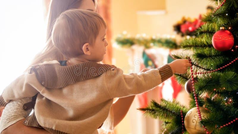 Φωτογραφία κινηματογραφήσεων σε πρώτο πλάνο του λατρευτού μικρού παιδιού που βάζει τις διακοσμήσεις στο δέντρο Chrismtas στοκ εικόνες με δικαίωμα ελεύθερης χρήσης