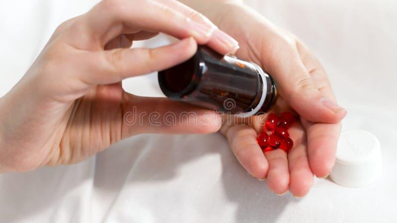 Φωτογραφία κινηματογραφήσεων σε πρώτο πλάνο του νέου μπουκαλιού τινάγματος γυναικών με τα χάπια και έκχυση τους σε διαθεσιμότητα στοκ εικόνα με δικαίωμα ελεύθερης χρήσης