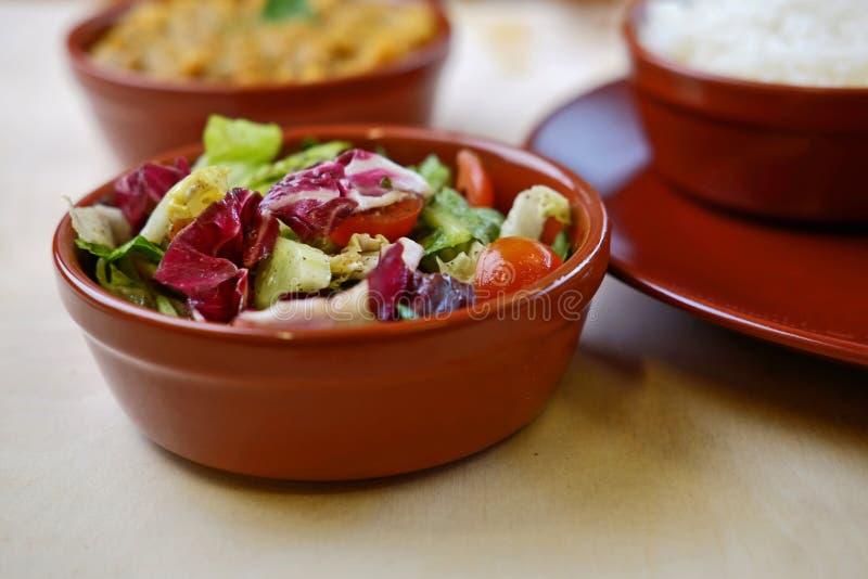 Φωτογραφία κινηματογραφήσεων σε πρώτο πλάνο του φυτικού salat στο κύπελλο με τα παραδοσιακά ινδικά πιάτα στο υπόβαθρο στοκ φωτογραφία