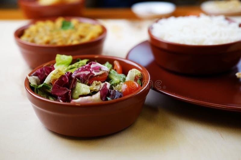 Φωτογραφία κινηματογραφήσεων σε πρώτο πλάνο του φυτικού salat στο κύπελλο με τα παραδοσιακά ινδικά πιάτα στο υπόβαθρο στοκ εικόνα