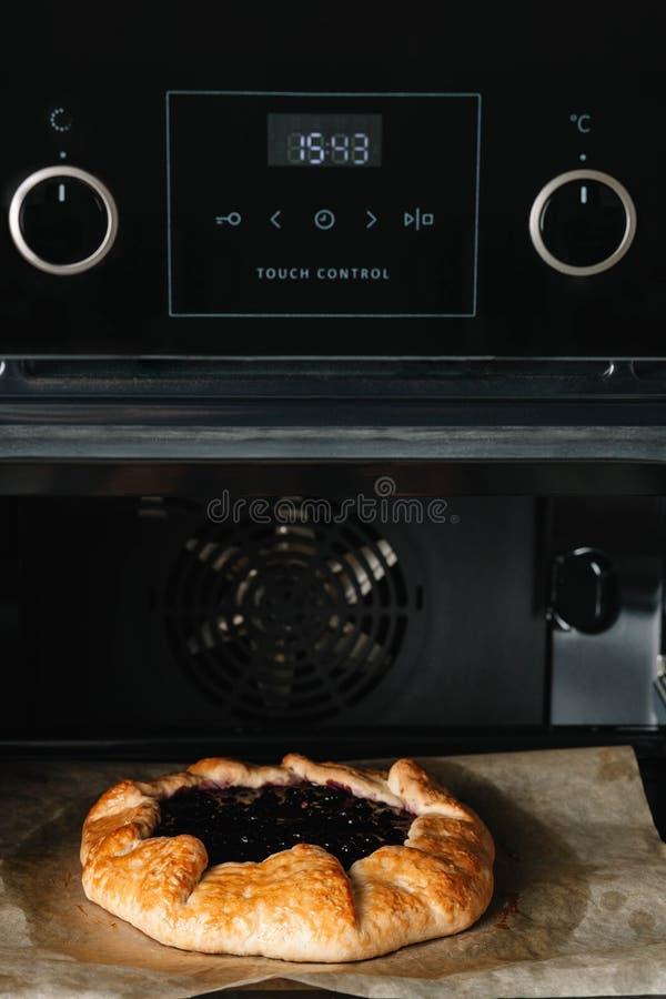 Φωτογραφία κινηματογραφήσεων σε πρώτο πλάνο του galette με το ψήσιμο μαύρων σταφίδων σε έναν φούρνο στοκ φωτογραφία με δικαίωμα ελεύθερης χρήσης