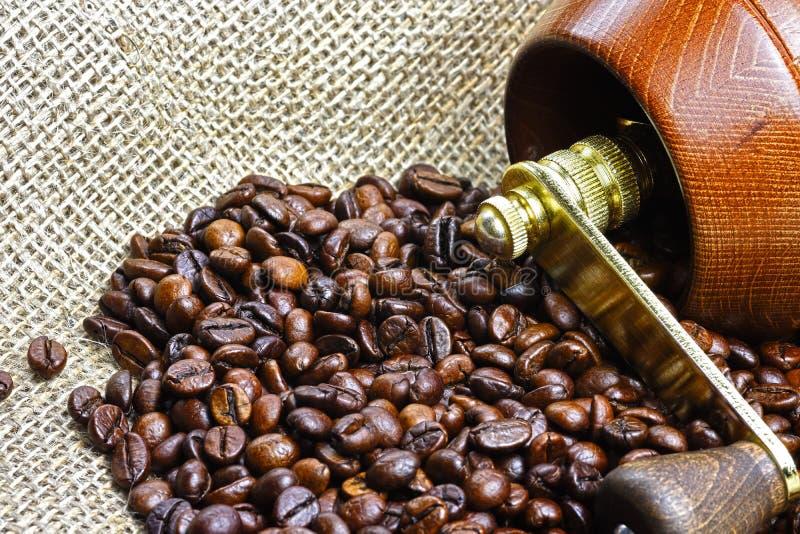 Φωτογραφία κινηματογραφήσεων σε πρώτο πλάνο των σιταριών του ψημένου μαύρου καφέ με ξύλινο mor στοκ φωτογραφίες