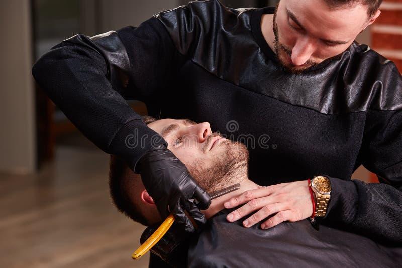 Φωτογραφία κινηματογραφήσεων σε πρώτο πλάνο του κυρίου ενώ κάνει τη διόρθωση γενειάδων για τον πελάτη στο σαλόνι barbershop στοκ εικόνα με δικαίωμα ελεύθερης χρήσης
