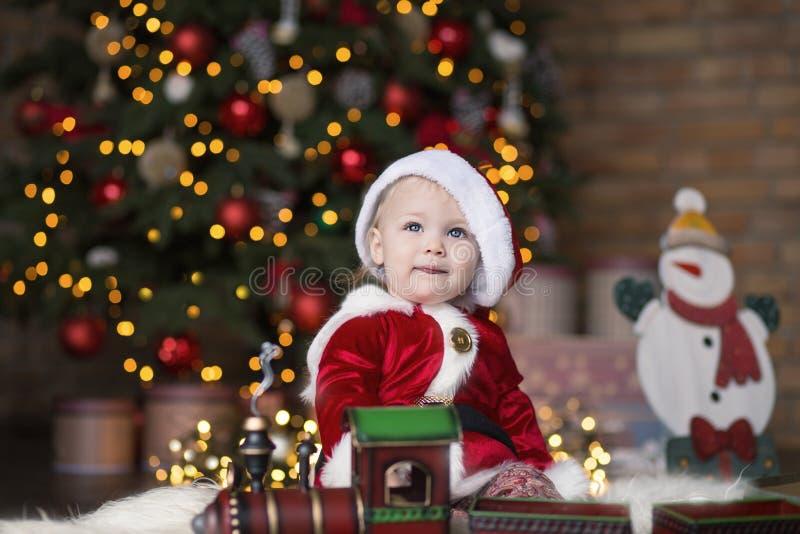 φωτογραφία μητέρων καπέλων Claus Χριστουγέννων μωρών που παίζει το santa του s που φορά μαζί στοκ εικόνες
