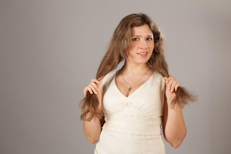 Φωτογραφία μόδας μιας νέας γοητευτικής γυναίκας με τη σγουρή τρίχα που φορά το άσπρο φόρεμα στοκ εικόνες