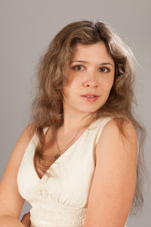 Φωτογραφία μόδας μιας νέας γυναίκας με τη σγουρή τρίχα που φορά το άσπρο φόρεμα στοκ φωτογραφία με δικαίωμα ελεύθερης χρήσης