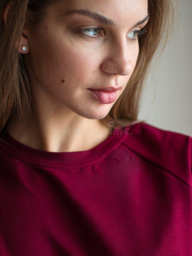 Φωτογραφία μόδας μιας όμορφης χαμογελώντας γυναίκας brunette σε μια κόκκινη τοποθέτηση πουλόβερ πέρα από το γκρίζο κενό υπόβαθρο στοκ φωτογραφία με δικαίωμα ελεύθερης χρήσης