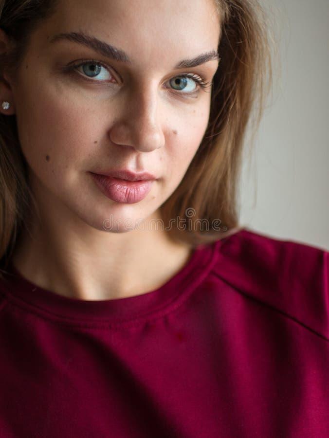 Φωτογραφία μόδας μιας όμορφης χαμογελώντας γυναίκας brunette σε μια κόκκινη τοποθέτηση πουλόβερ πέρα από το γκρίζο κενό υπόβαθρο στοκ εικόνες
