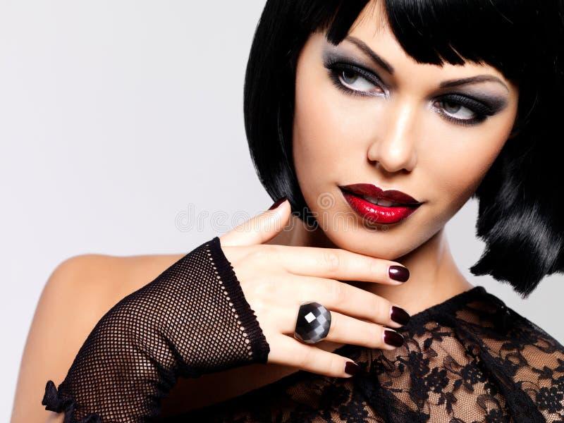 Φωτογραφία μόδας μιας όμορφης γυναίκας brunette με τον πυροβολισμό hairstyle. στοκ φωτογραφία