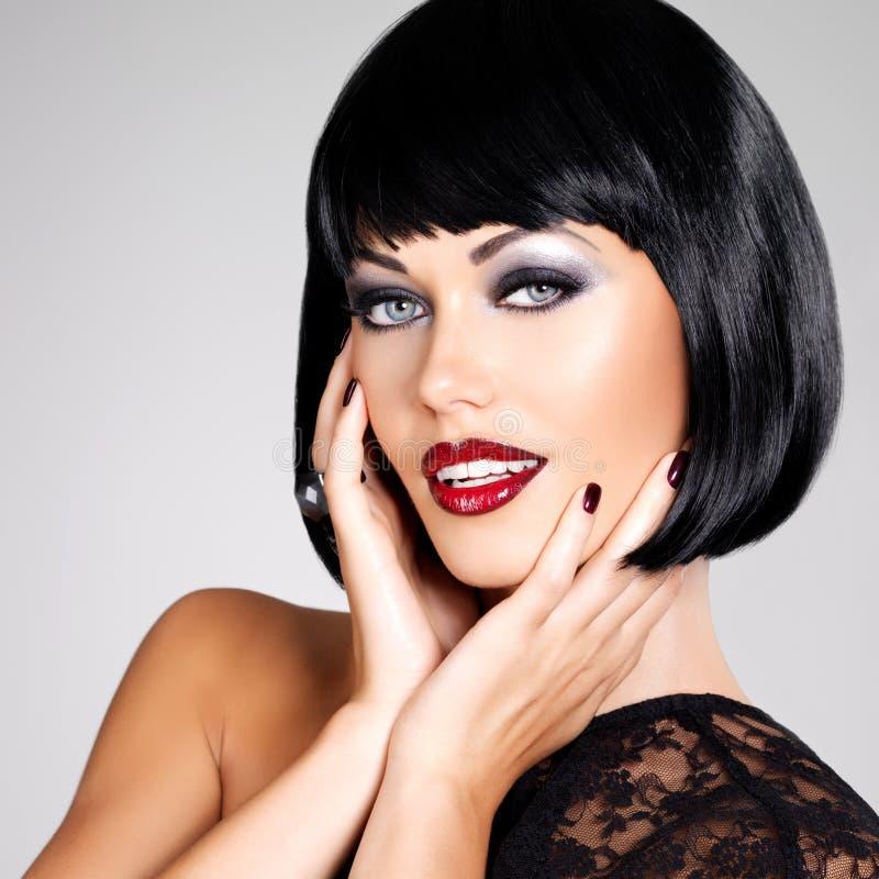 Φωτογραφία μόδας μιας όμορφης γυναίκας brunette με τον πυροβολισμό hairstyle. στοκ εικόνες