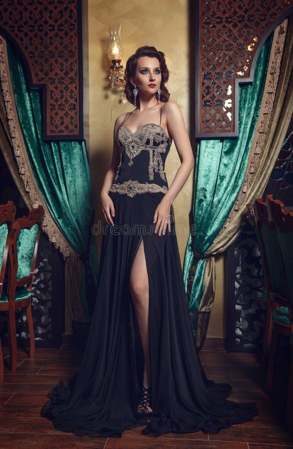 Φωτογραφία μόδας της νέας θαυμάσιας γυναίκας στο μαύρο φόρεμα στοκ εικόνες