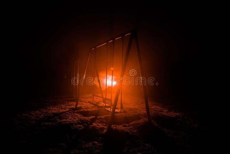 Φωτογραφία νύχτας της ταλάντευσης μετάλλων που στέκεται υπαίθρια στη νύχτα με την ομίχλη και το υπερφυσικό τονισμένο φως στο υπόβ στοκ εικόνα με δικαίωμα ελεύθερης χρήσης