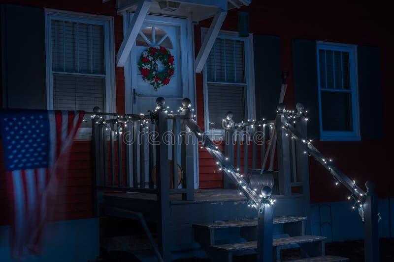 Φωτογραφία νύχτας του μέρους ενός μικρού απλού σπιτιού που διακοσμείται με τις γιρλάντες Χριστουγέννων και ένα στεφάνι Η σημαία τ στοκ εικόνες