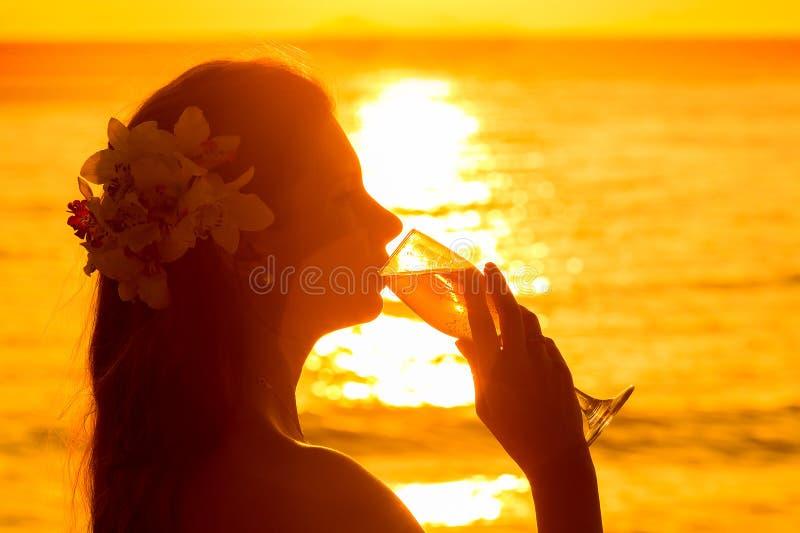 Φωτογραφία σκιαγραφιών μιας σαμπάνιας κατανάλωσης γυναικών από ένα γυαλί στο s στοκ εικόνες
