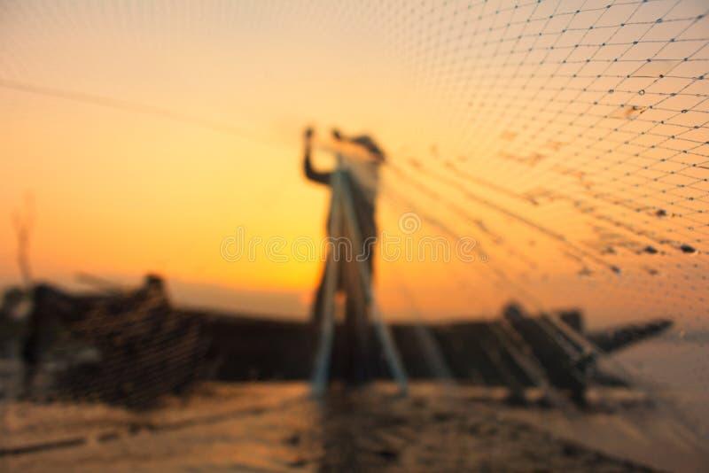 Φωτογραφία σκιαγραφιών Ο παλαιός ψαράς που πετά το δίχτυ στο ηλιοβασίλεμα στοκ εικόνα