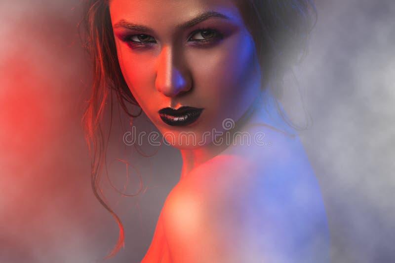 Φωτογραφία στούντιο της προκλητικής γυναίκας στον καπνό στοκ φωτογραφία με δικαίωμα ελεύθερης χρήσης