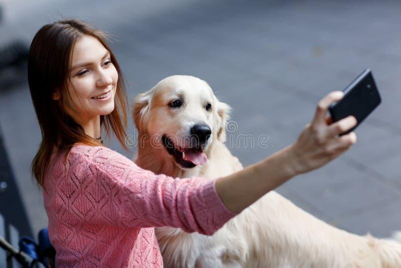 Φωτογραφία της γυναίκας στον πάγκο που κάνει selfie με το σκυλί στοκ εικόνες