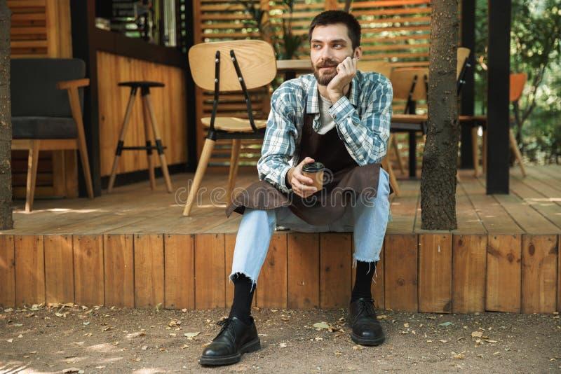 Φωτογραφία της ελκυστικής συνεδρίασης ατόμων σερβιτόρων στο ξύλινο πάτωμα λειτουργώντας στον καφέ ή το καφέ υπαίθριο στοκ φωτογραφία με δικαίωμα ελεύθερης χρήσης