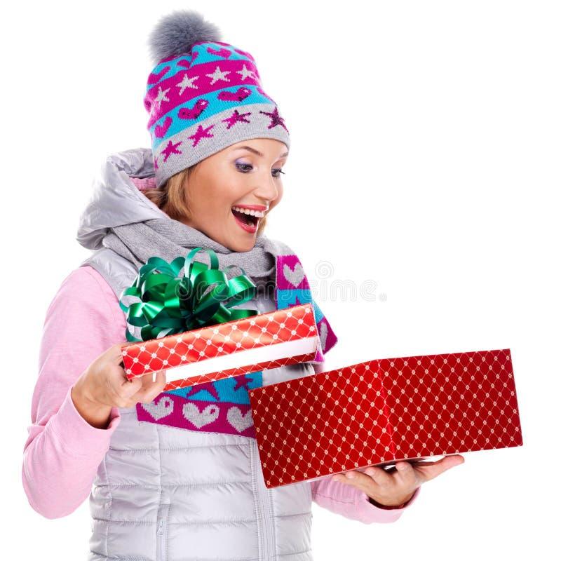 Φωτογραφία της ευτυχούς έκπληκτης γυναίκας με ένα δώρο Χριστουγέννων στοκ φωτογραφία