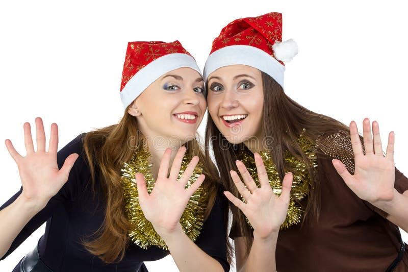 Φωτογραφία της ευτυχούς νέας γυναίκας δύο στα καπέλα Χριστουγέννων στοκ φωτογραφία
