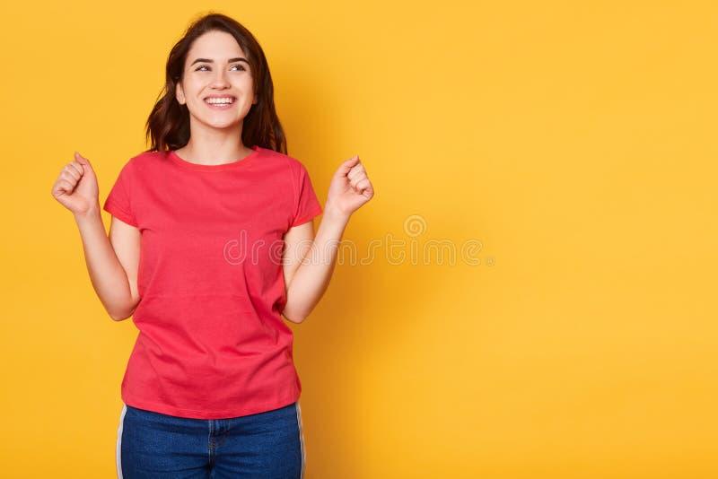Φωτογραφία της ευτυχούς νέας όμορφης γυναίκας που σφίγγει την πυγμή χαμογελώντας και επάνω απομονωμένος πέρα από το κίτρινο υπόβα στοκ φωτογραφία με δικαίωμα ελεύθερης χρήσης