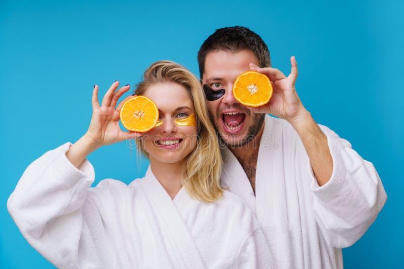 Φωτογραφία της ευτυχών γυναίκας και του άνδρα με τα πορτοκάλια κοντά στο μάτι στοκ εικόνες με δικαίωμα ελεύθερης χρήσης