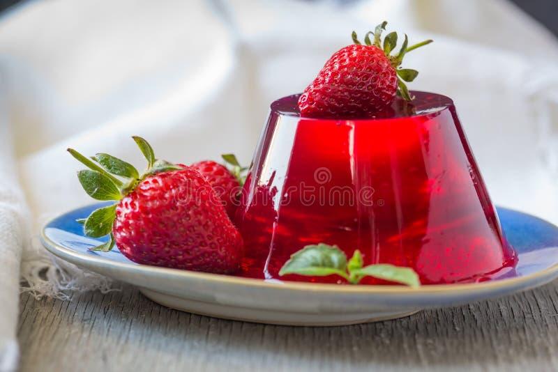 Φωτογραφία της ζελατίνας φρούτων με τη φρέσκια φράουλα r Ζελατίνα φραουλών στο άσπρο πιάτο Θερινό επιδόρπιο με τα φρούτα στοκ φωτογραφία με δικαίωμα ελεύθερης χρήσης