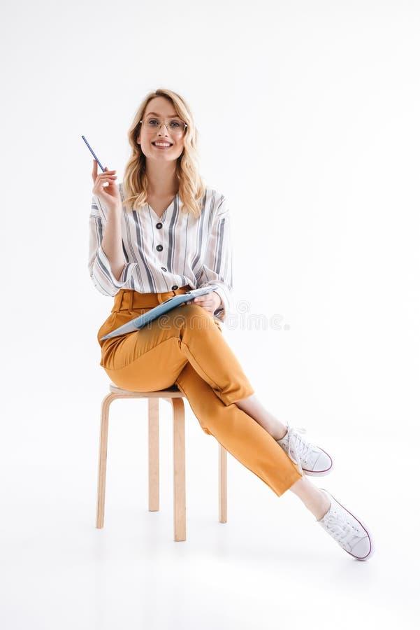 Φωτογραφία της καυκάσιας χαριτωμένης γυναίκας που φορά τα γυαλιά που κάθονται στην καρέκλα και που κρατούν την περιοχή αποκομμάτω στοκ εικόνες