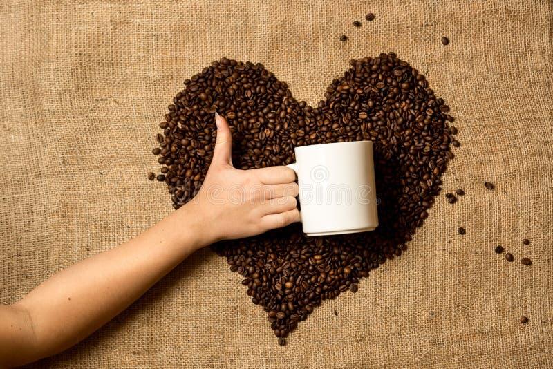 Φωτογραφία της κούπας εκμετάλλευσης γυναικών ενάντια στην καρδιά φιαγμένη από φασόλια καφέ στοκ φωτογραφία