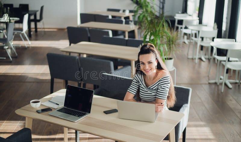 Φωτογραφία της νέας θηλυκής συνεδρίασης χαμόγελου σε έναν καφέ που χρησιμοποιώντας το φορητό προσωπικό υπολογιστή που κουβεντιάζε στοκ φωτογραφία