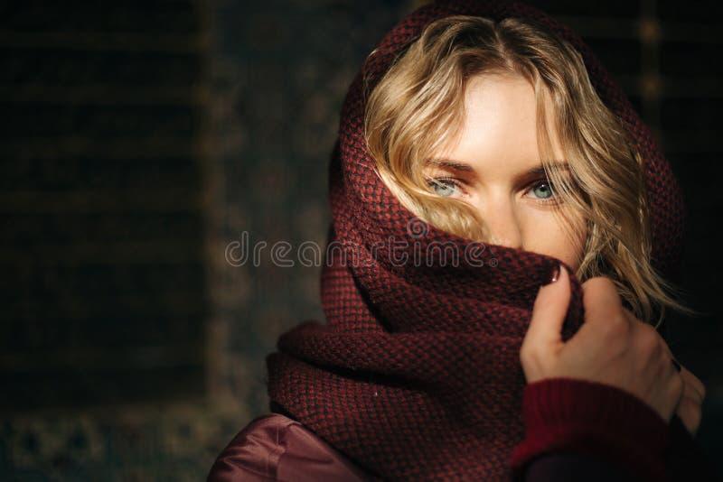 Φωτογραφία της νέας ξανθής γυναίκας με καλυμμένο το μαντίλι πρόσωπο ενάντια στον καφετή τοίχο στοκ εικόνα