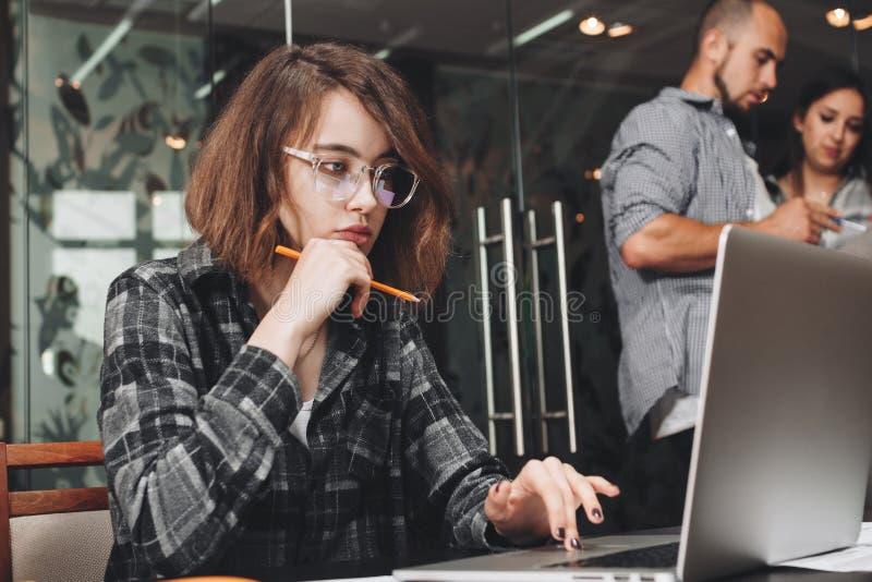 Φωτογραφία της σκεπτικής επιχειρησιακής γυναίκας που φορά τα γυαλιά λειτουργώντας στοκ φωτογραφία με δικαίωμα ελεύθερης χρήσης