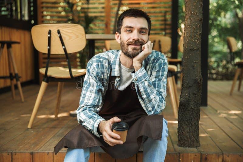 Φωτογραφία της συνεδρίασης ατόμων σερβιτόρων χαμόγελου στο ξύλινο πάτωμα λειτουργώντας στον καφέ ή το καφέ υπαίθριο στοκ φωτογραφία με δικαίωμα ελεύθερης χρήσης
