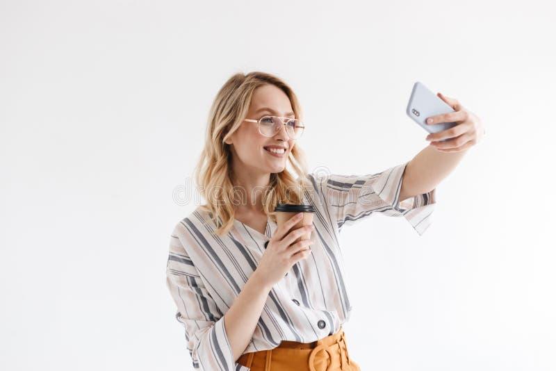 Φωτογραφία της χαμογελώντας νέας γυναίκας που φορά τα γυαλιά που παίρνουν selfie τη φωτογραφία και που κρατούν το φλυτζάνι εγγράφ στοκ φωτογραφίες με δικαίωμα ελεύθερης χρήσης