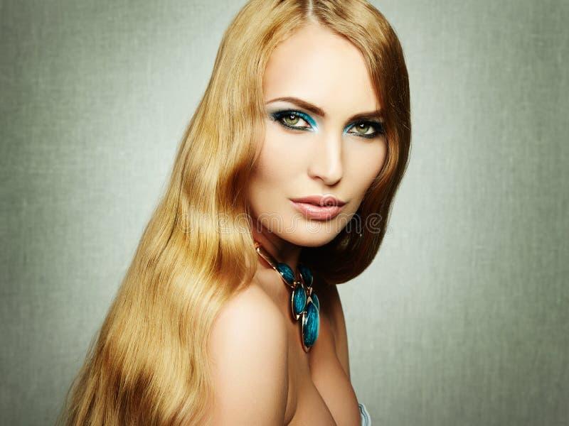 Φωτογραφία της όμορφης γυναίκας με τη θαυμάσια τρίχα. Τέλειο makeup στοκ εικόνα