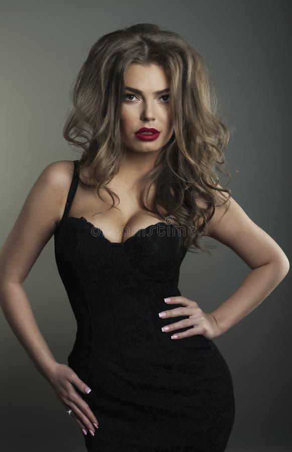 Φωτογραφία της όμορφης νέας γυναίκας στα συμπαθητικά μαύρα ενδύματα και το κόκκινο χείλι στοκ εικόνα